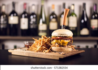 Close up of a delicious cheeseburger, tomatoes, and french fries. Pickles and cheese dripping off the side. Knife stabbed through a burger on a kitchen table.