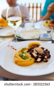 Close up of delicious grilled octopus and hummus served for lunch or dinner at outdoor restaurant