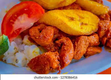 Close up of delicious hornado, ecuadorian traditional typical andean food served with corn, potato, sweet plantain, salad, avocado in a white plate over a wooden table