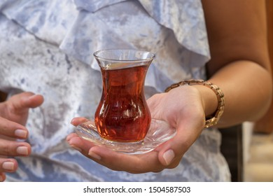 Close up of delicious red Turkish tea with traditional pear shaped glass in the woman hand, Turkey