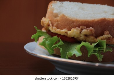Close up the delicious sandwich with omelette (eggs), lettuce, cheese and tomatoes. Sandwich on the white plate. Fast, tasty, hearty and nutritious breakfast. Brown background.