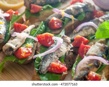 Close up of a delicious sardines tapas with rocket, tomatoes and red onions