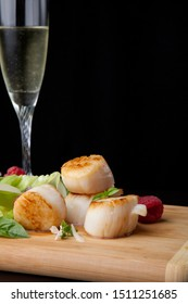 Close up of delicious savory fried scallops salad with fresh raspberry, basil, green lettuce, and red onion. Glass of Champagne. Over black background. Contemporary appetizers series.