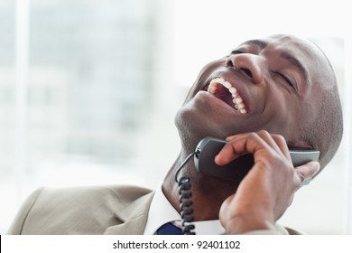 Close up of a delighted businessman on the phone in his office