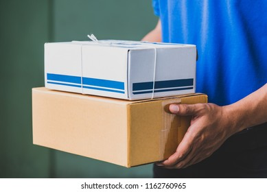 Close up Delivery man in blue uniforms holding parcel cardboard box.