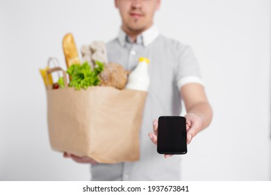 close up of delivery man giving the paper bag with products and asking for signature on the phone