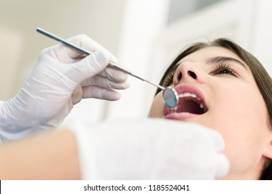 Close up of dentist examining patient's teeth in clinic.