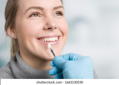 Close up of dentist using shade guide at woman's mouth to check veneer of teeth for bleaching