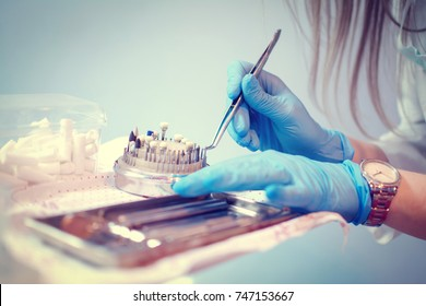 Close up of dentist's hands in surgical gloves working with dental instruments.