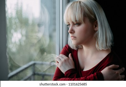 Close up of depressed young blond woman near window at home. Sadness, nostlagic, depression.