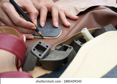 Close up designer's hands drawing or drafting woman shoes template for cutting leather with tools and accessories on table.