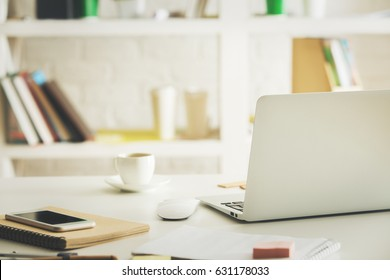 Close up of desk with laptop, smartphone, supplies, coffee cup and other items. Workplace concept