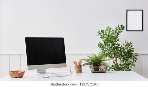 Close up desktop screen on the white table and decorative object on the desk. White background and frame detail.