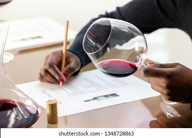 Close up detail of african hands holding red wine glass.Wine enthusiast  evaluating red wine at wine tasting. Woman taking notes with decanter at table.