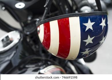 close up detail of american flag motorcycle helmet hanging from motorcycle handlebars