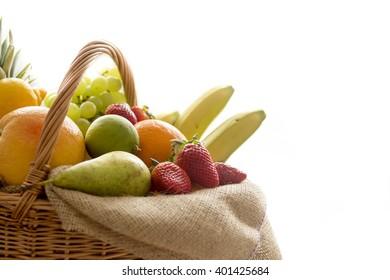 Close up detail of a basket full of fresh bio fruit (banana, apple, pear, grapes, orange, pineapple...) on a light background â??Â� high key photography