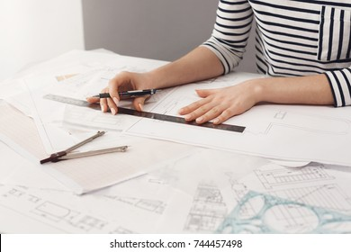 Close up detail of beautiful young female architect in striped shirt sitting at desk, holding pen and ruler in hands, making blueprints, working on new project at home. Business and art