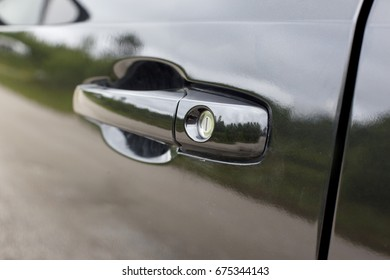 a close up or detail of black door handle on a shiny vehicle or car, with a lock or key hole