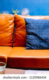 Close up detail of blue pillow on leather sofa