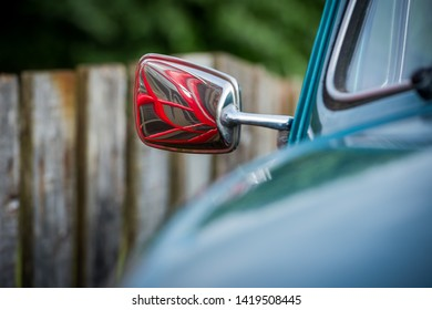 A close up detail of a blue vintage car, with the chrome rear-view mirror reflecting an old red english telephone booth