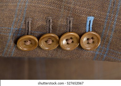 Close up detail of a brown checked tailored business suit sleeve with buttons