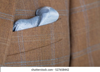 Close up detail of a brown checked tailored business suit with pocket and blue hankerchief