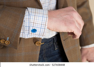 Close up detail of a brown checked tailored business suit sleeve with button holes and checked shirt