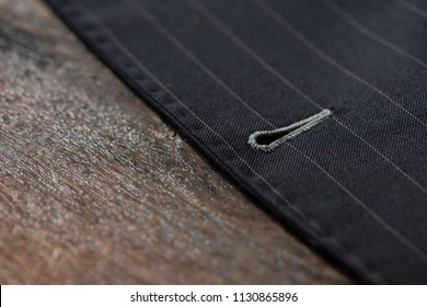 Close up detail of button hold stitching for custom made jacket on old wooden table, professional tailor concept.Bespoke jacket.Pay attention in every details.