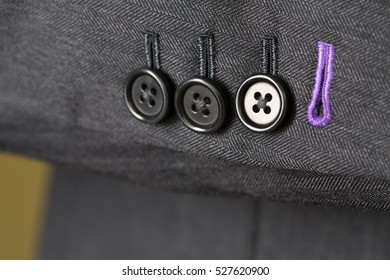Close up detail of buttons and cuff on a grey tailored business suit