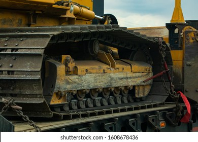 Close up detail of a continuous tread, aka caterpillar track, on a heavy plant machine. Tracked construction vehicle chained to a loader for transport