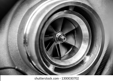 Close up detail of a diesel engine turbocharger with fan blades and center axle - selective focus on center axle