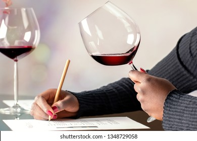 Close up detail of  female african hands holding glass of red wine. Academy student evaluating wine at table.