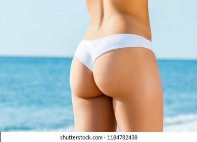 Close up detail of female buttock in white bikini outdoors. Rear view of slim woman with tanned skin tone.