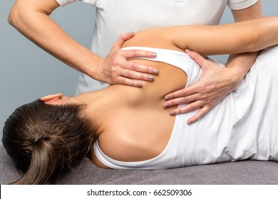 Close up of detail of female physiotherapist doing shoulder blade treatment on patient.