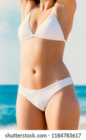 Close up detail of female torso in white bikini outdoors.Slim muscular body with healthy skin tone.