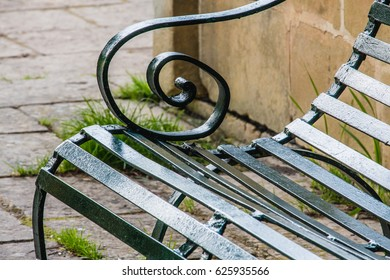 Close up detail of a green painted metal bench in a park. Curved arm rest. Ta Qali National Park, Malta