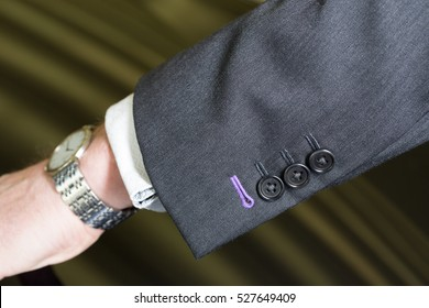 Close up detail of a grey tailored business suit sleeve with buttons and wrist watch