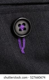 Close up detail of a grey tailored business suit button on trouser pocket