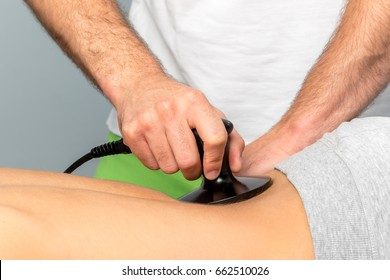 Close up detail of hand applying electrotherapy on spine with apparatus.