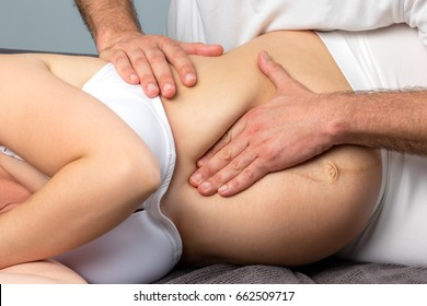 Close up detail of hands doing osteopathic on abdomen of pregnant woman.