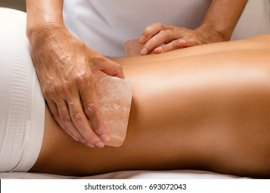 Close up detail of himalayan salt stone massage. Therapist massaging lower back of woman with hot salt brick.