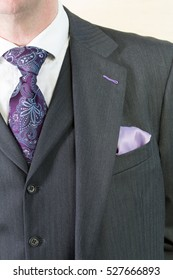 Close up detail image of bespoke tailored grey business suit with purple tie, waistcoat and shirt