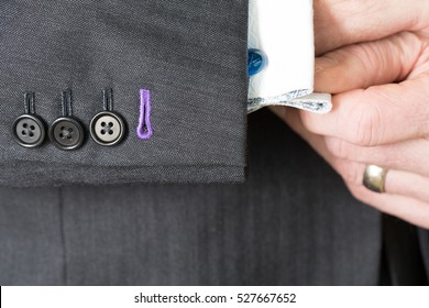 Close up detail image of bespoke tailored grey business suit sleeve buttons and cuff