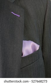 Close up detail image of bespoke tailored grey business suit with purple handkerchief