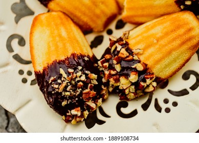 close up detail of madeleine cookies dipped in chocolate and chopped nuts on fancy cutwork metal dessert plate