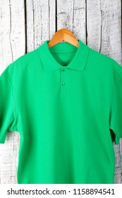 Close Up Detail Mens Green Polo Shirt Short Sleeve front view on rustic white wood background. Design sweatshirt mockup for print.