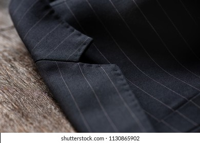 Close up detail of notch lapel    and stitching for custom made jacket on old wooden table, professional tailor concept.Bespoke jacket.Pay attention in every details.