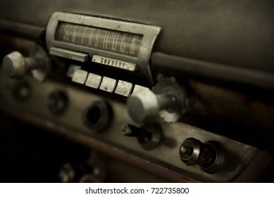 close up detail of old dashboard push button radio in junk American muscle car.