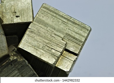 Close up detail on a cube of pyrite isolated single shiny mineral stone, fool's gold, cubic gems, on white limbo background