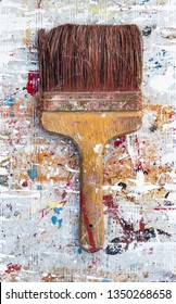 Close up detail on Old used grungy paint brush on vibrant colourful paint splattered background